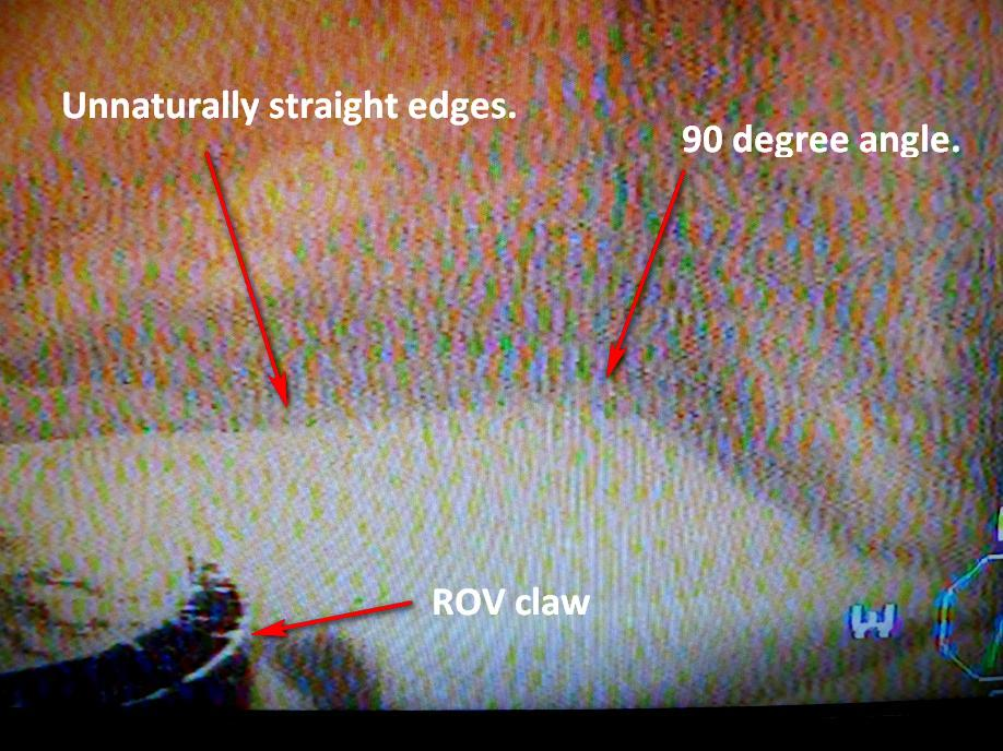 Photograph of screen from ROV camera showing more straight edges and 90 degree angles. Click for larger image.